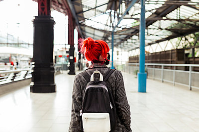 Redheaded woman with backpack on railroad platform during COVID-19 - p300m2286659 by Manu Reyes