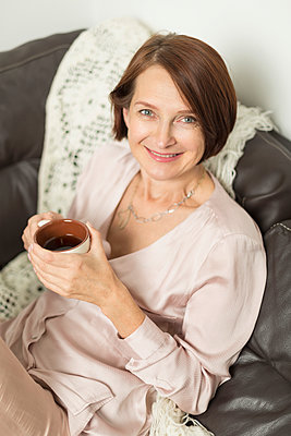 Portrait of mature woman smiling while sitting with hot drink - p301m2039701 by Vladimir Godnik