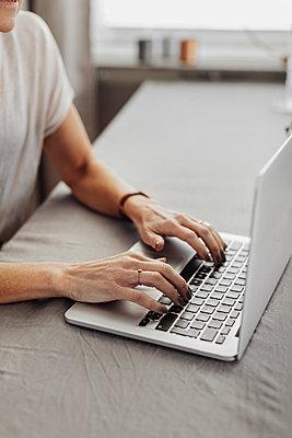 Woman's hand on laptop keyboard - p312m2299752 by Plattform