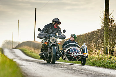 Senior man and grandson riding motorcycle and sidecar along rural road - p429m1226934 by GS Visuals