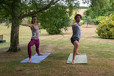 Man and woman doing yoga in garden, practicing warrior pose - p429m2032201 by Image Source