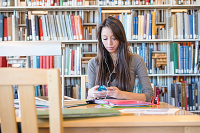Student listening to earphones in library - p555m1453297 by John Fedele