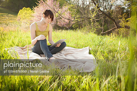 A young woman sitting in an open space, a grass field, on a blanket, reading from a digital tablet.  - p1100m876956f by Norah Levine