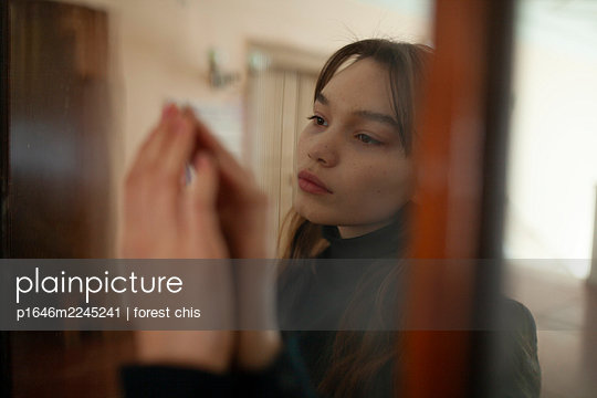 Young woman touches mirror glass with her hand - p1646m2245241 by Slava Chistyakov