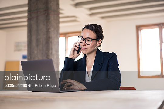 Businesswoman talking on mobile phone while working on laptop at office - p300m2226975 by Robijn Page