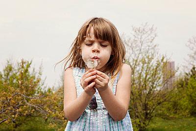 Cute girl blowing dandelion on field against clear sky - p1166m1151420 by Cavan Images