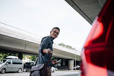 Young businessman using remote control key of car - p300m1535916 by Kniel Synnatzschke