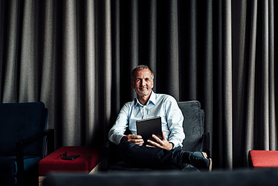 Smiling male senior business professional holding digital tablet while sitting on armchair in office cafeteria - p300m2266315 by Gustafsson
