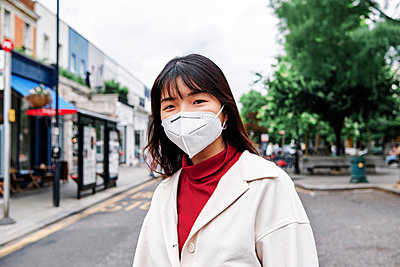 Woman with protective face mask in city during coronavirus - p300m2293268 by Angel Santana Garcia