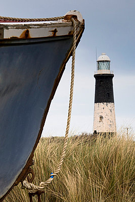 Abandoned boat and lighthouse, Humberside, England - p4426837f by Design Pics