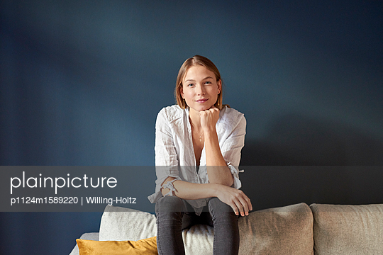Young woman sitting on sofa - p1124m1589220 by Willing-Holtz