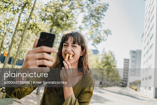 Portrait of brunette woman, taking a selfie, rabbit teeth with french fries - p300m2155486 by Kniel Synnatzschke