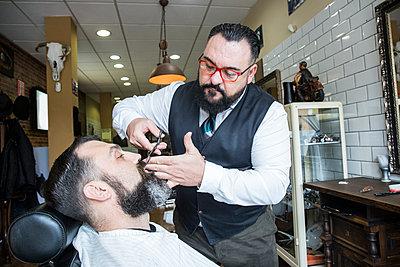 Barber cutting man's beard - p300m1205761 by Andrés Benitez