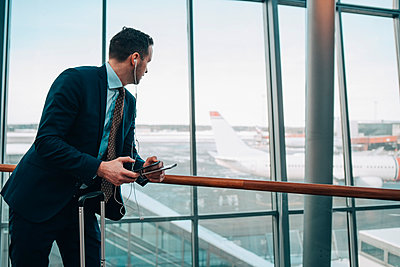 Businessman looking at airplane through window while using mobile phone in airport - p426m1580127 by Maskot