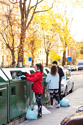 Male with female environmentalist throwing plastic bottles in garbage can - p426m2213243 by Maskot