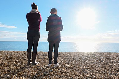 Rear view of two young adult sisters looking out at sunlit sea - p429m1095360f by Simon Potter