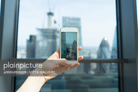 UK, London, woman's hand taking photo of skyscrapers of financial district with cell phone - p300m2016228 von VITTA GALLERY