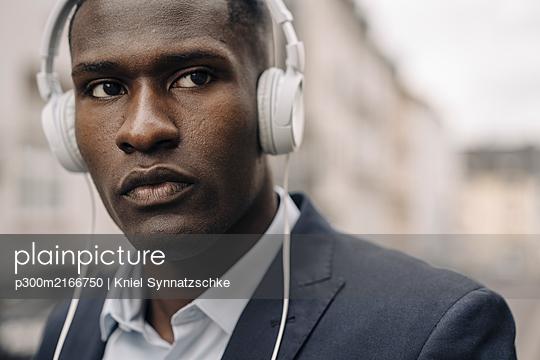 Portrait of young businessman wearing white headphones - p300m2166750 by Kniel Synnatzschke