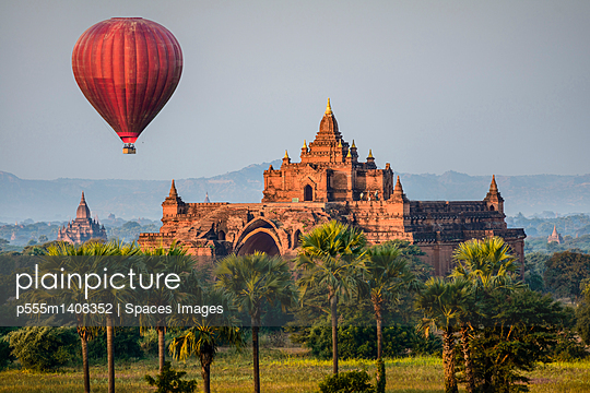 Hot air balloon flying over temple - p555m1408352 by Spaces Images