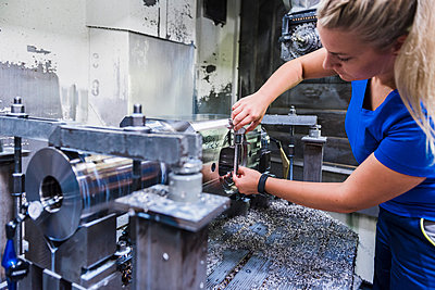 Woman working on machine in industrial factory - p300m1537462 by Daniel Ingold
