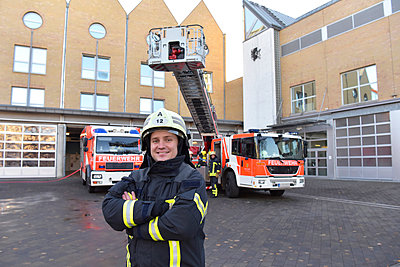 Portrait of smiling firefighter in front of fire engine with colleagues in background - p300m2081114 by lyzs