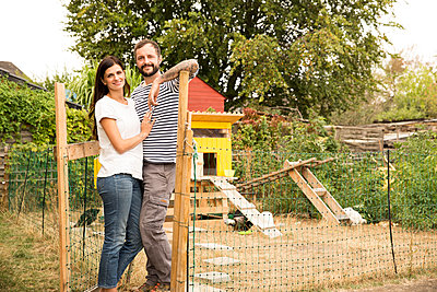 Portrait of confident couple standing at chickenhouse in garden - p300m2083659 by Michelle Fraikin