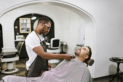 Barber cutting beard of a customer in barber shop - p300m2113944 von Hernandez and Sorokina