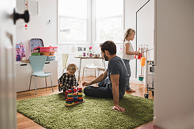 Father and daughters playing with toys in playroom at home - p426m1451757 by Maskot