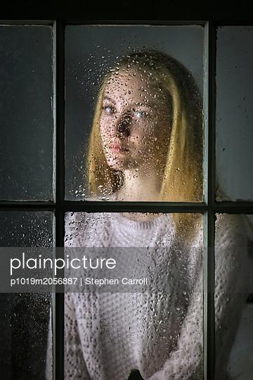 Weiblicher Teenager hinter einer nassen Fensterscheibe - p1019m2056887 von Stephen Carroll