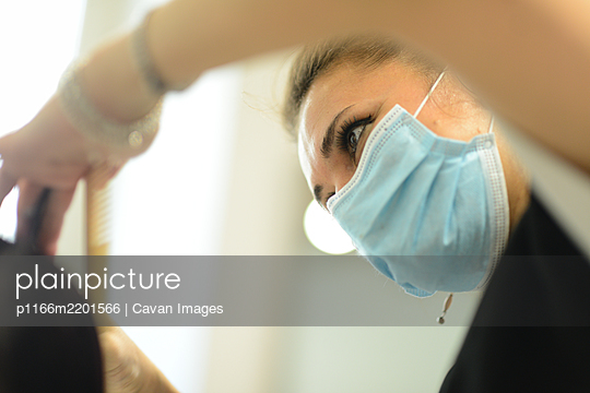 Female hair stylist at work wearing face mask while styling young gir - p1166m2201566 by Cavan Images