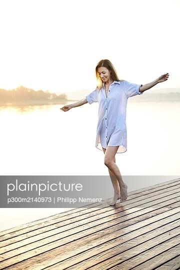 Mature woman balancing on jetty at a lake at sunrise - p300m2140973 by Philipp Nemenz