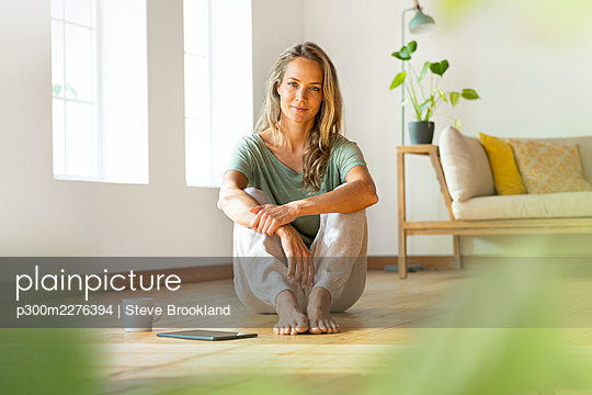 Confident woman in loungewear sitting on floor by digital tablet and coffee mug at home - p300m2276394 by Steve Brookland
