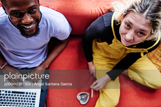 Couple smiling while sitting on sofa at home - p300m2287324 by Angel Santana Garcia