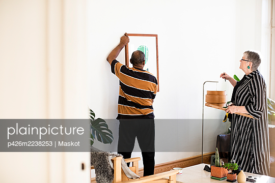 Elderly man adjusting painting while standing against woman in living room - p426m2238253 by Maskot
