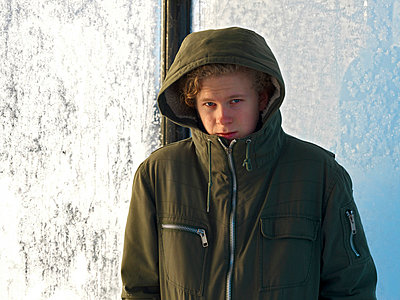 Portrait of a teenage boy in green hood jacket waiting at a bus stop - p1025m788972f by Peo Quick