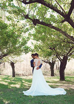 bride and bride entwined under the trees - p1521m2126370 by Charlotte Zobel