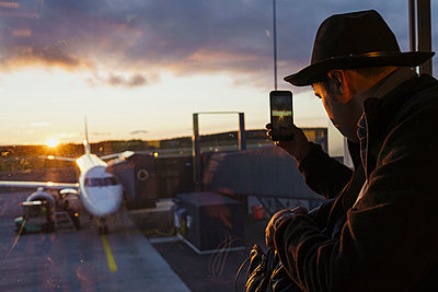 Young man behind window taking cell phone picture of plane at the airport - p300m2042243 by Kike Arnaiz
