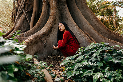 Young asian woman in front of a tree with very large roots - p300m2167544 von Tania Cervián