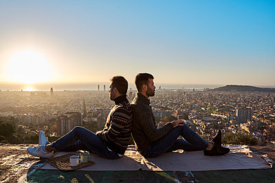 Gay couple sitting back to back on observation point during sunrise, Bunkers del Carmel, Barcelona, Spain - p300m2256688 by Veam