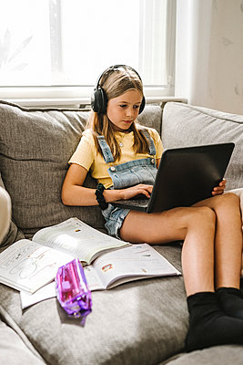 Caucasian girl e-learning through laptop at home - p426m2238290 by Maskot