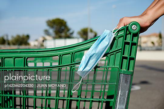 Man pushing a shopping cart wearing his face mask in his hand - p1423m2204330 by JUAN MOYANO