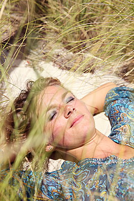 Woman sleeping in the dunes - p045m907333 by Jasmin Sander