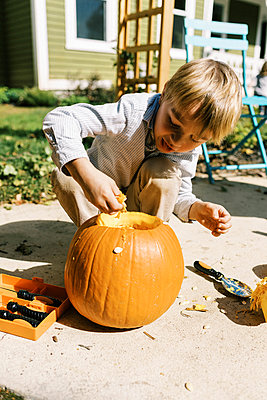 Child carving out pumpkins for halloween on their patio - p1166m2218610 by Cavan Images