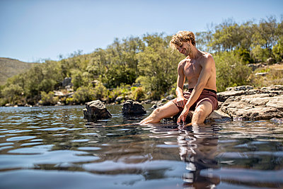 Junger Mann badet seine Füße im Fluss - p1355m1574197 von Tomasrodriguez