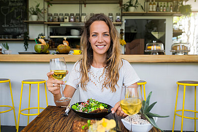 Portrait of smiling woman holding glass of wine in a cafe - p300m1549493 by Steve Brookland