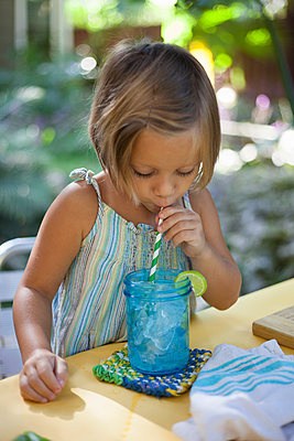 Girl drinking ice water through straw - p924m1468699 by Kinzie Riehm