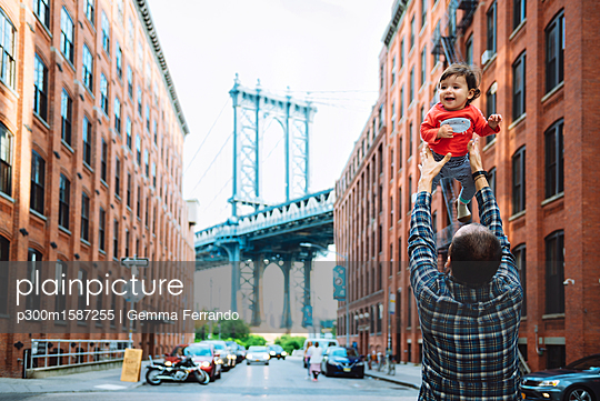 USA, New York, New York City, Father playing with baby in Brooklyn with Manhattan Bridge in the background - p300m1587255 von Gemma Ferrando