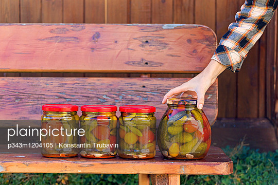 Woman Holding A Jar Of Homemade Pickle On Wooden Bench - p343m1204105 by Konstantin Trubavin