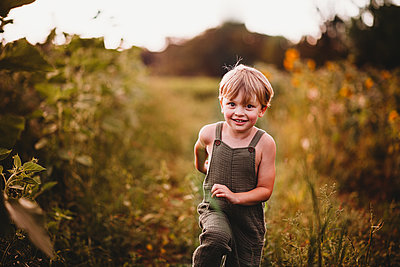 Happy boy running in a flower field wearing green dungarees - p1166m2212682 by Cavan Images