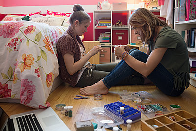 Girls making jewelry on bedroom floor - p1192m1158035 by Hero Images